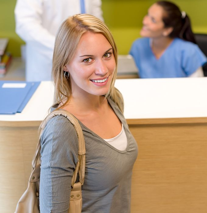 Smiling woman at dental office reception desk