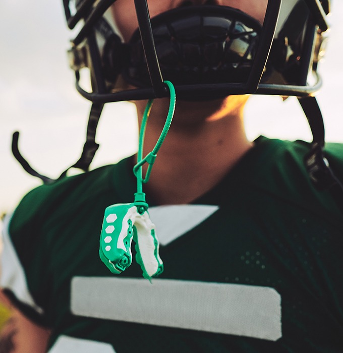 Athletic mouthguard hanging from football helmet