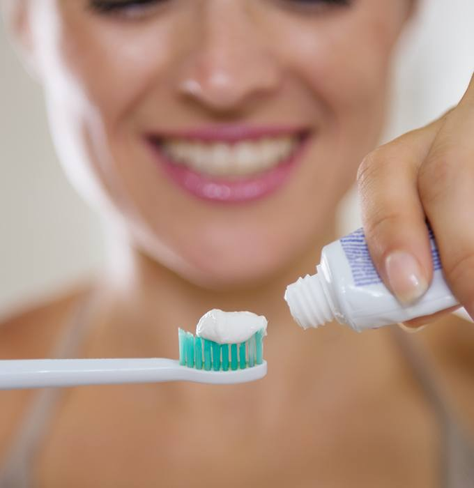 Patient placing toothpaste on toothbrush during dental hygiene routine